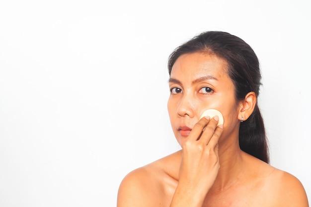 Mulher asiática que olha a câmera e que aplica o pó da fundação em sua cara. conceito de beleza Foto Premium