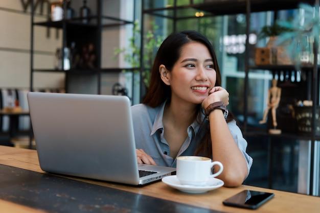 Mulher asiática que trabalha e bebe café no café com sorriso de computador portátil e trabalho feliz Foto Premium