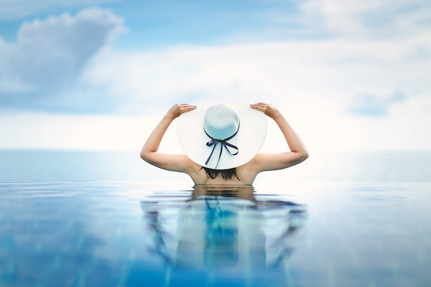 Mulher asiática relaxar na piscina na praia Foto Premium