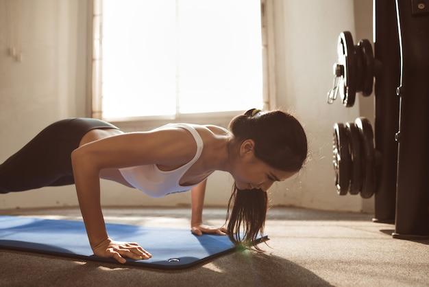 Mulher asiática são flexões no ginásio Foto Premium