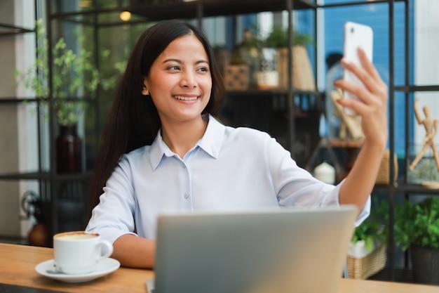 Mulher asiática selfie com telefone móvel na cafeteria café sorriso e cara feliz Foto Premium