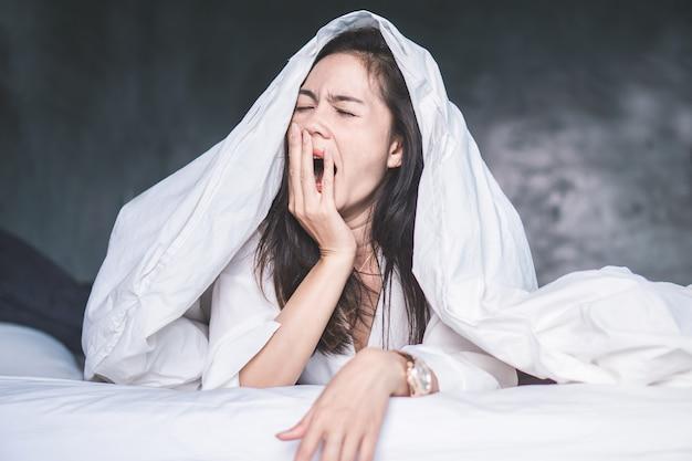 Mulher asiática sem sono, bocejando na cama Foto Premium
