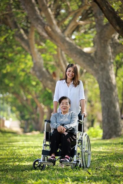 Mulher asiática sênior, sentado na cadeira de rodas com a família daugther sorriso feliz rosto no parque verde Foto Premium