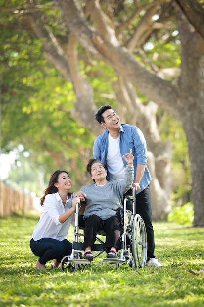 Mulher asiática sênior, sentado na cadeira de rodas com a família feliz sorriso cara no parque verde Foto Premium
