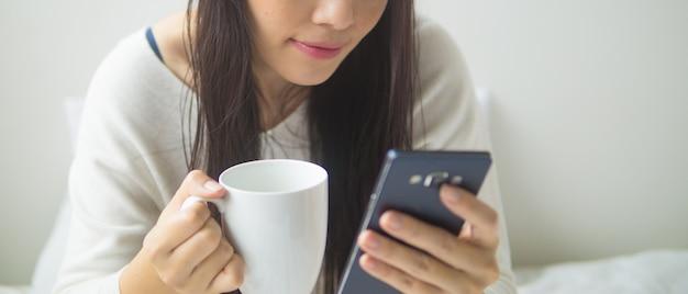 Mulher asiática, sentado na cama, mensagens de texto em seu smartphone e beber café em casa no quarto Foto Premium