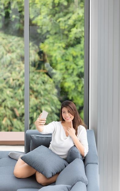Mulher asiática sentar no sofá com o celular Foto Premium