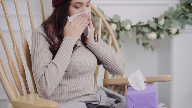 Mulher asiática sentir dor de cabeça envolto em manta cinza assoar o nariz e usar o tecido Foto gratuita