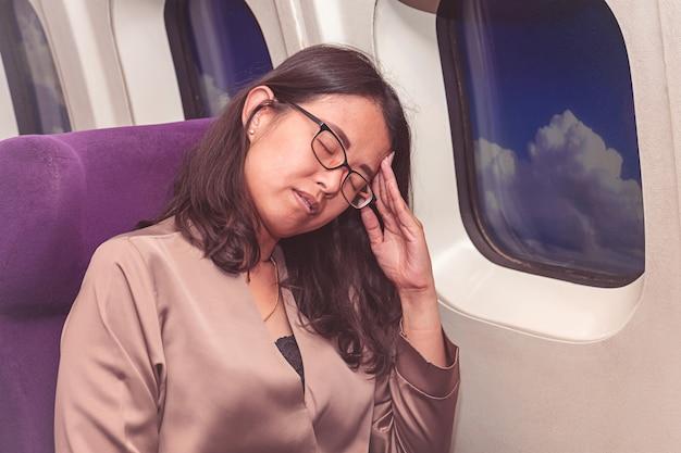 Mulher asiática sofre de dor de cabeça dentro do avião Foto Premium