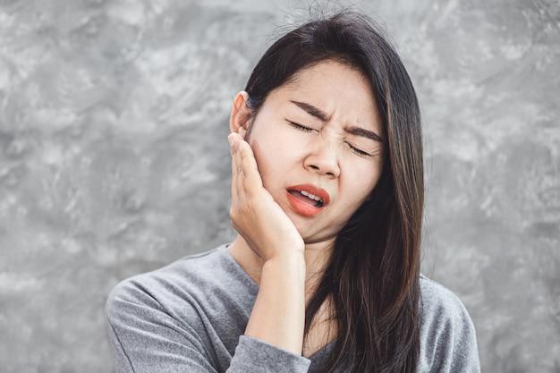 Mulher asiática, sofrendo de problema de dor de dente Foto Premium