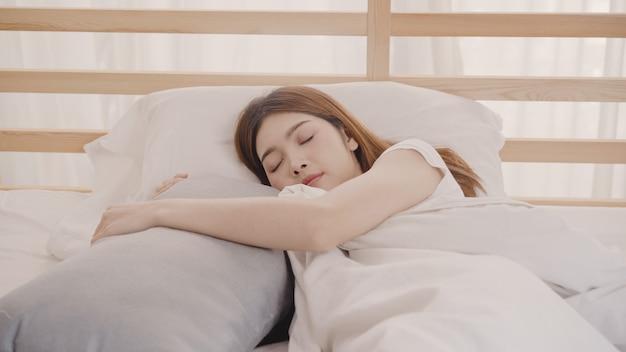 Mulher asiática sonhando enquanto dorme na cama no quarto Foto gratuita
