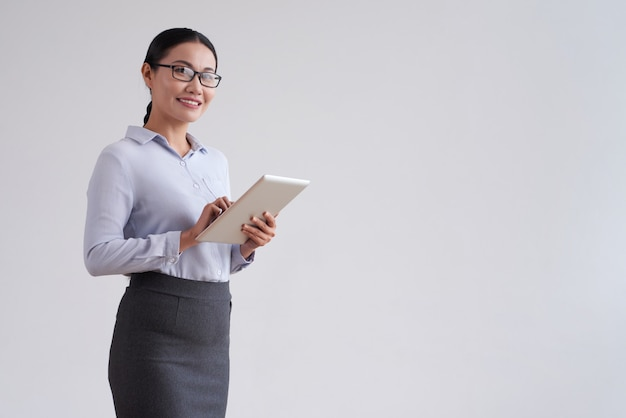 Mulher asiática sorridente em copos, segurando o computador tablet e olhando para a câmera Foto gratuita