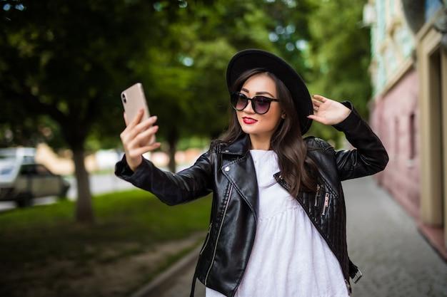 Mulher asiática sorridente muito bonita tomando selfie na rua da cidade Foto gratuita