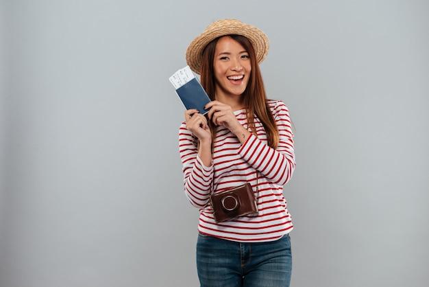 Mulher asiática sorridente na camisola e chapéu com câmera retro Foto gratuita