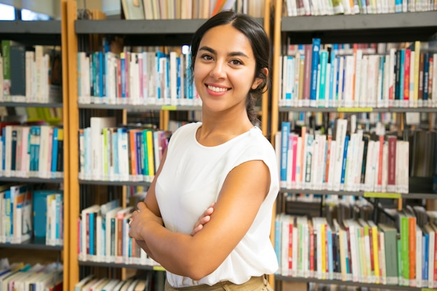Mulher asiática sorridente posando na biblioteca pública Foto gratuita