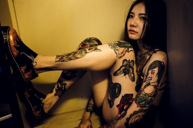 Mulher asiática tatuada sentado em uma caixa Foto gratuita