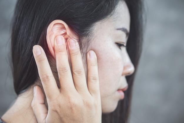 Mulher asiática tem dor no ouvido, conceito de zumbido Foto Premium