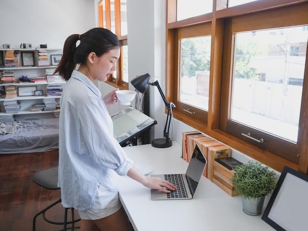 Mulher asiática tomando café na sala de trabalho Foto Premium
