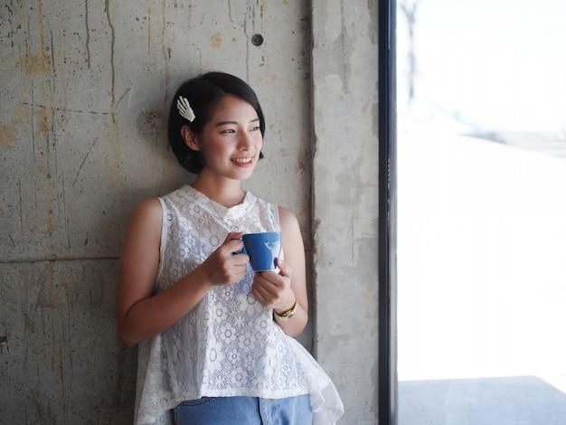 Mulher asiática tomando café no café Foto Premium