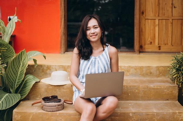 Mulher asiática trabalhando no laptop em um período de férias e sentado nas escadas Foto gratuita