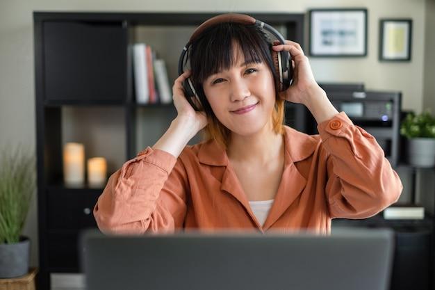 Mulher asiática trabalhar com o computador em casa. ouvindo aula on-line. programa de áudio com fone de ouvido. Foto Premium