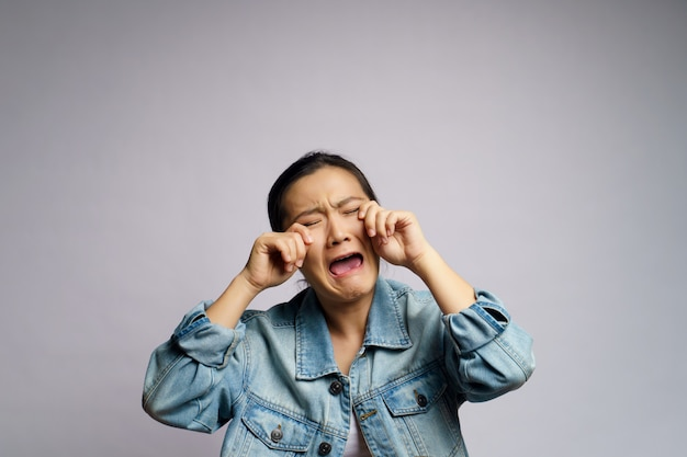 Mulher asiática triste e chorando em pé isolado. Foto Premium