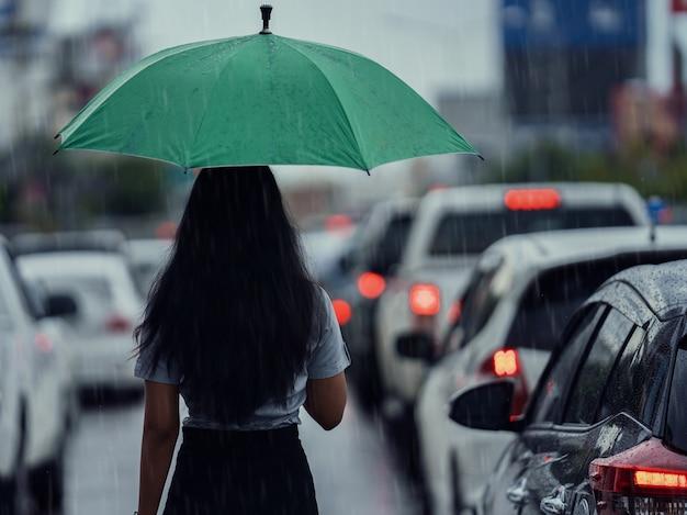 Mulher asiática usa guarda-chuva enquanto chove. ela está atravessando a rua Foto gratuita