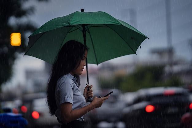Mulher asiática usa o guarda-chuva enquanto chove. ela está atravessando a rua. e usar o telefone Foto gratuita