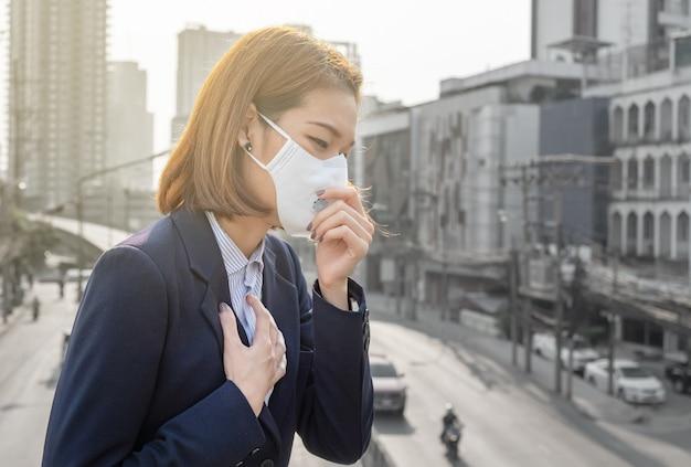 Mulher asiática usando a máscara de proteção respiratória n95 contra a poluição do ar pm2.5 e dor de cabeça sufocar Foto Premium