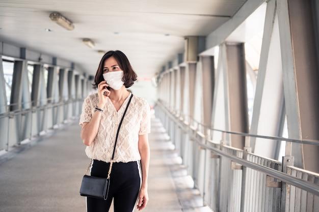 Mulher asiática usando máscara para evitar o crepúsculo da tarde. 2.5 poluição atmosférica e coronavírus ruins, covid-19 se espalhando pela ásia usando telefonemas no celular. Foto Premium