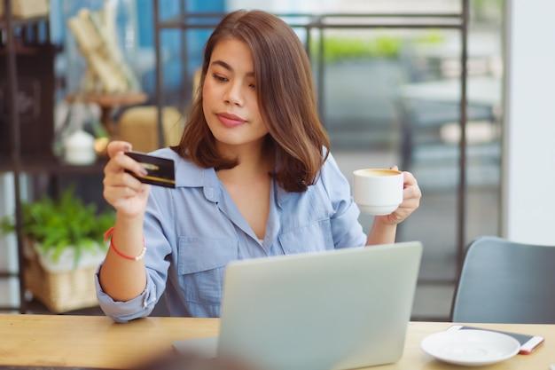 Mulher asiática, usando telefone celular com cartão de crédito e computador portátil para fazer compras de pagamento on-line no café café com amigos Foto Premium