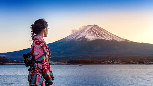 Mulher asiática vestindo quimono tradicional japonês na montanha fuji. pôr do sol no lago kawaguchiko, no japão. Foto gratuita