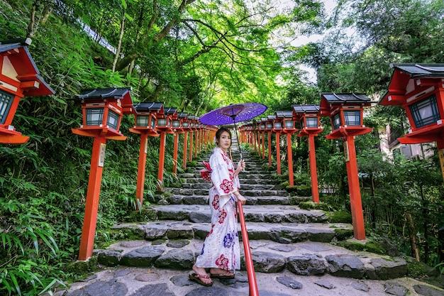 Mulher asiática vestindo quimono tradicional japonês no santuário de kifune em kyoto, japão. Foto gratuita