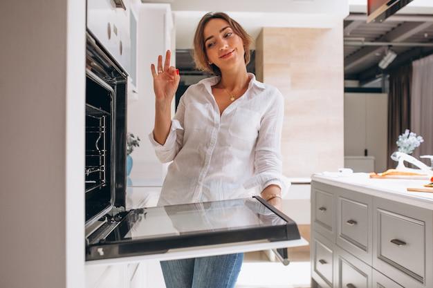Mulher assando na cozinha e olhando para o forno Foto gratuita