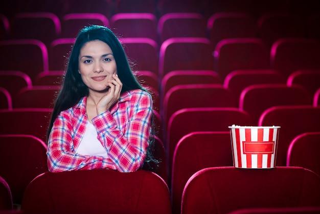 Mulher assistindo filme no cinema Foto gratuita