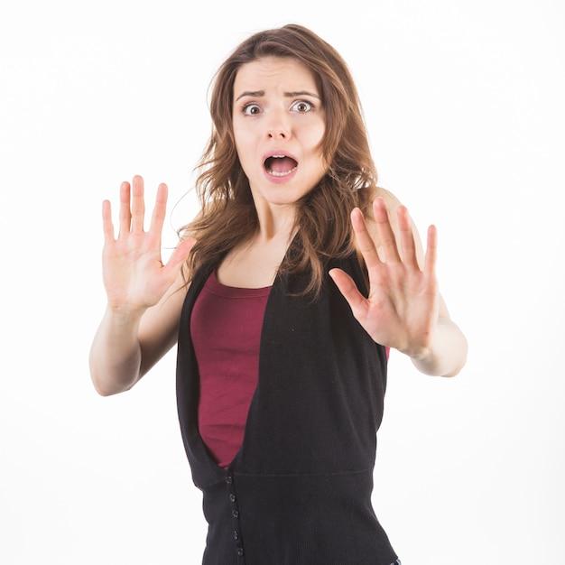 Mulher assustada, defendendo-se contra o fundo branco Foto gratuita