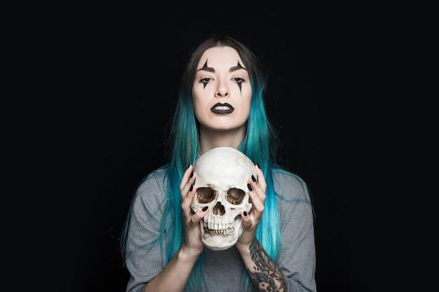 Mulher assustadora, segurando o crânio humano Foto gratuita