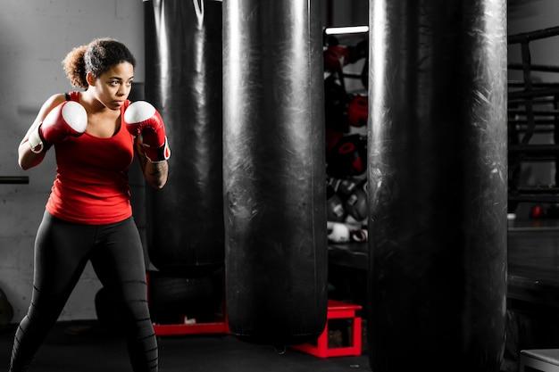 Mulher atlética boxe em um centro de treinamento Foto gratuita