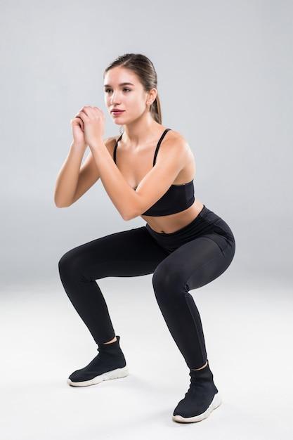 Mulher atlética desportiva de cócoras fazendo abdominais no ginásio isolado sobre a parede branca Foto gratuita