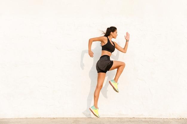 Mulher atlética em roupas esportivas, malhando e correndo Foto Premium