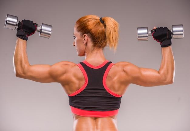 Mulher atlética está bombeando os músculos com halteres. Foto Premium