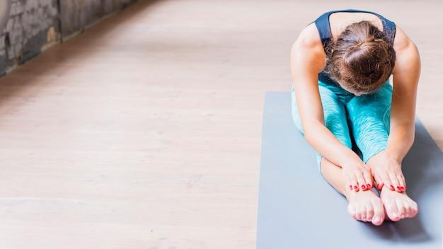 Mulher atlética fazendo exercícios de alongamento no tapete de ioga Foto gratuita