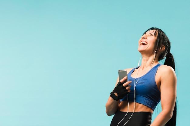 Mulher atlética feliz curtindo música em fones de ouvido Foto gratuita