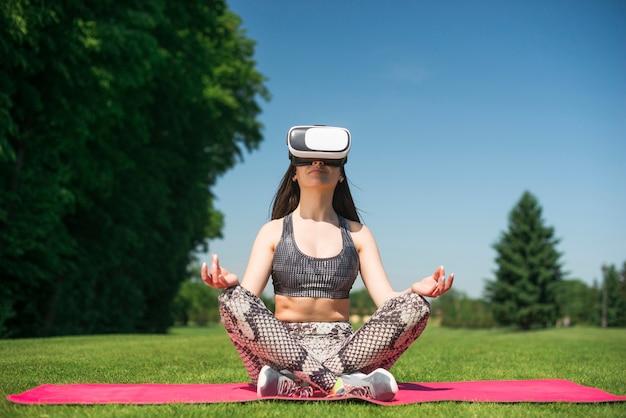 Mulher atlética, usando um óculos de realidade virtual ao ar livre Foto gratuita