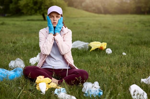 Mulher atônita e chocada sentada no parque na grama verde com as palmas das mãos nas bochechas, vestindo roupas casuais, cercada de lixo, precisa coletar todo o lixo. Foto gratuita