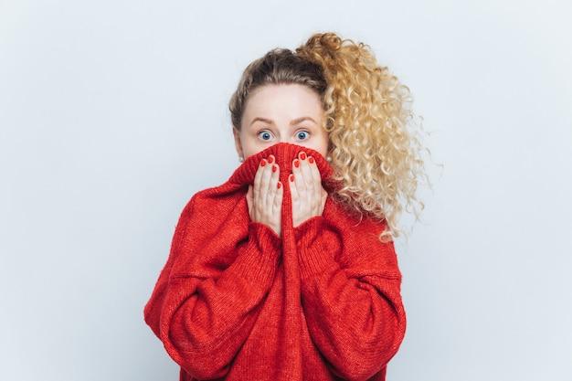 Mulher atordoada assustada vê sua fobia, cobre o rosto com gola de suéter vermelho Foto Premium