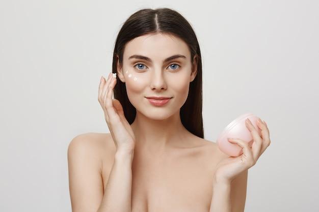 Mulher atraente aplicar creme facial, produto anti-envelhecimento Foto gratuita