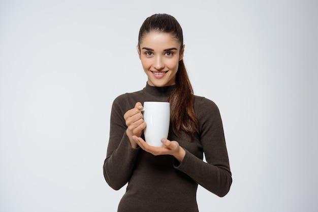 Mulher atraente, bebendo chá, segurando xícara Foto gratuita