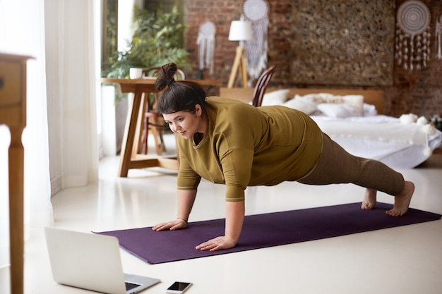 Mulher atraente com excesso de peso descalço, fazendo prancha na esteira de ioga, enquanto treinava dentro de casa, assistindo a vídeos online via laptop. esportes, bem-estar, tecnologia e conceito de estilo de vida ativo e saudável Foto gratuita