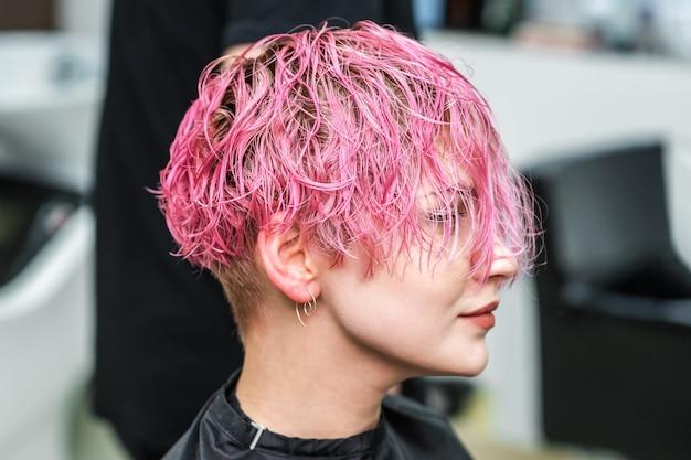 Mulher atraente com glamour molhado cabelo rosa curto no salão de beleza. Foto Premium