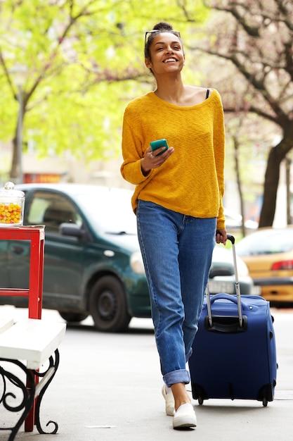 Mulher atraente com mala e celular na rua da cidade Foto Premium